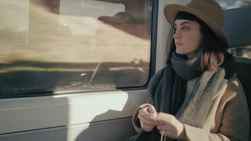 Short haired girl in hat travels in train, puts headphonesand in her ears, turns on music on iphone and smiles listening song, looking through window and browsing playlist, close up view