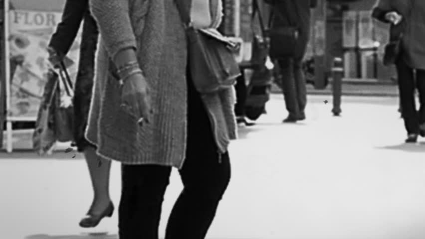 Slow motion of busy intersection with still woman smoking cigarette and pedestrians around walking in a rush - vintage 8mm film look