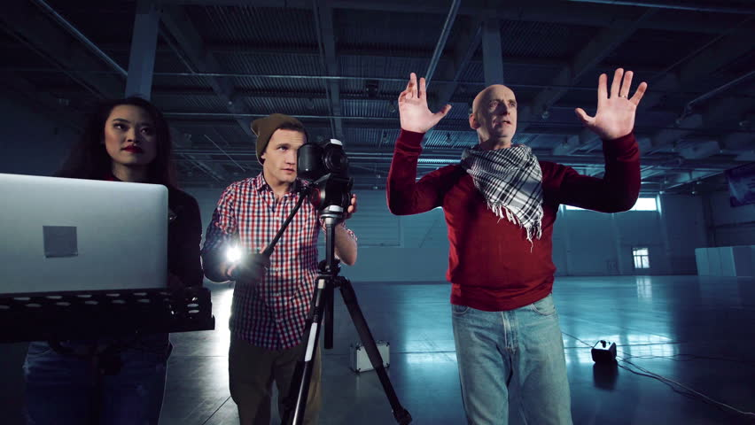 A group of people shooting a video blog in a studio hangar.