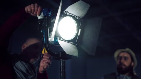 Male filmmakers adjusting professional light stand in studio together, with lighting on and blinking at camera.