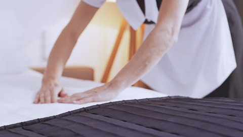 Middle-aged Caucasian chambermaid in uniform making bed in the morning in slowmotion