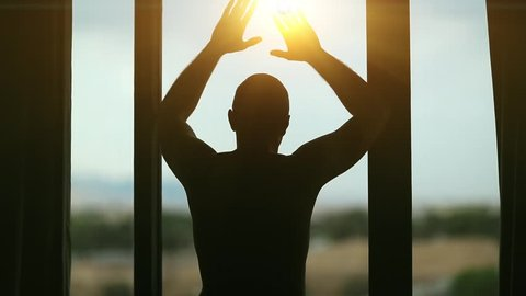 Man opens the curtains in the morning and looks out the window. Young man opens big window curtains and lets the sun light in the room