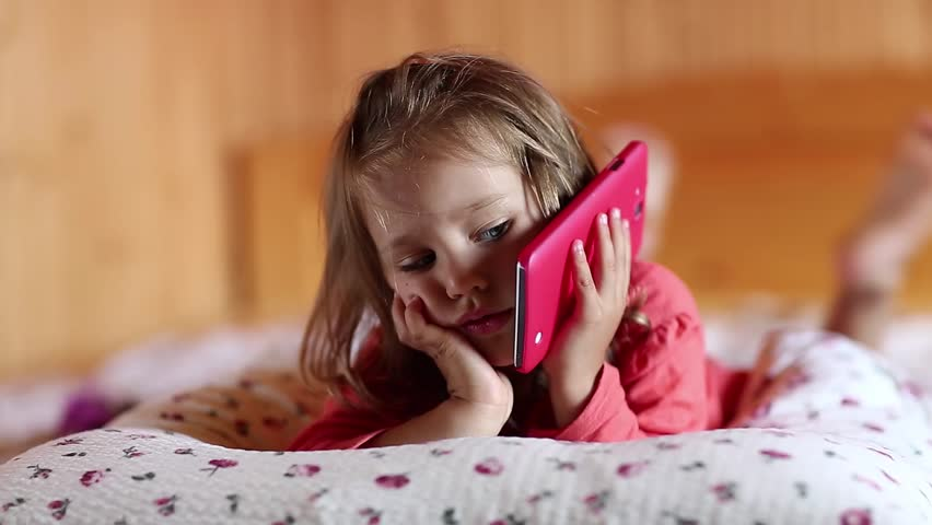 Funny little girl with big red smartphone lies on the bed. Little girl lies on the pillow, holds in hand red mobile phone and talks with mother