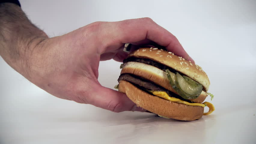 Male places down an unappetizing burger high in  cholesterol and saturated fats onto a white background   Shutterstock HD Video #24097309