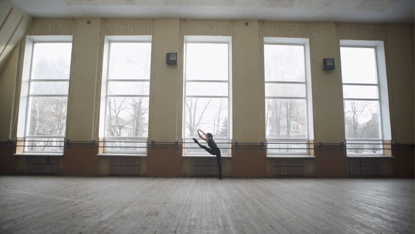 Young girl doing a work-out in the dancehall making stretching exercise in black clothes. Wide angle.