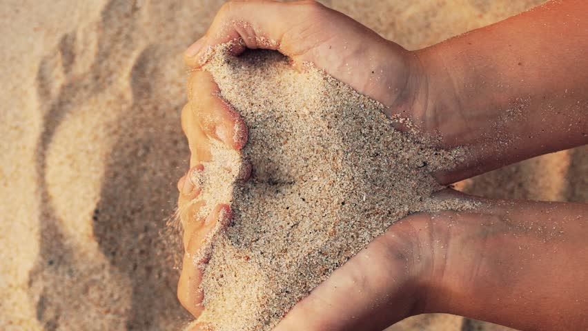 Close up view of sand in the hands of women. The concept of the passing time of life