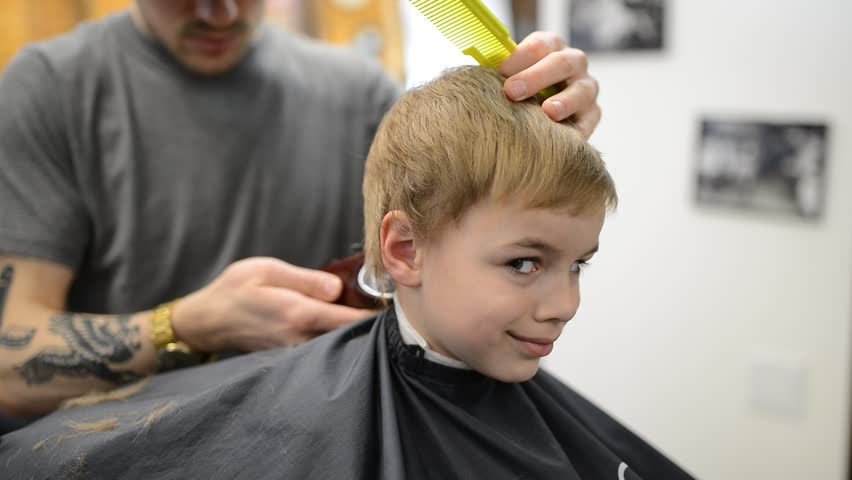 Haircutter male with client child in the barbers. Hairdresser using trimmer in barbershop. Happy cute kid sitting on the chair in hairdressing salon.