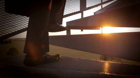 Slow motion of climbing up the stairs. Young businessman taking challenges and making a career. Morning sun in the background.