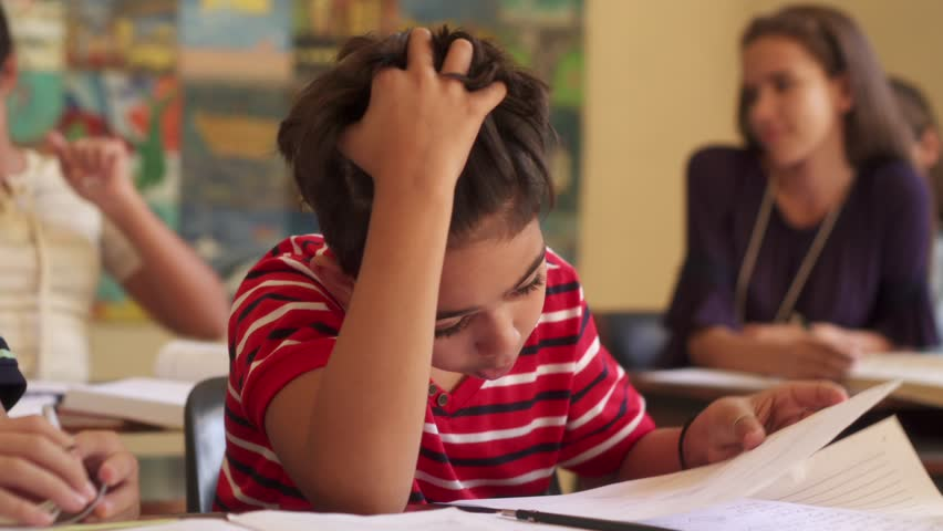 Young people and education. Group of hispanic students in class at school during lesson. Sad male student depressed for bad grades on test, unhappy boy with papers