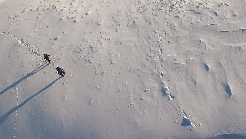 Aerial footage of two men hikers climbing up on the mountain at winter.