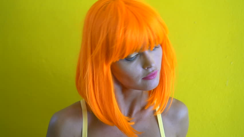 Closeup portrait of woman with colourful makeup in futuristic style shaking her hair and smiling over yellow wall background. Creative look of woman in yellow bra and orange wig - slow motion video