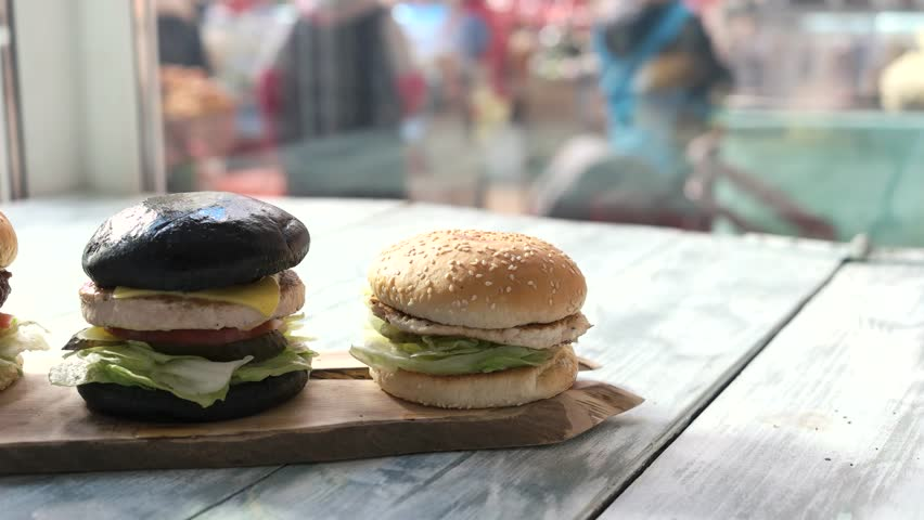 Three hamburgers on wooden board. Burgers in cafe. | Shutterstock HD Video #24171319