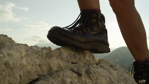 SLOW MOTION, CLOSE UP: Detail of vintage leather mountaineering boots. Unrecognizable adventurous female hiker climbing rocky mountains and walking uphill on amazing sunny summer day in European Alps