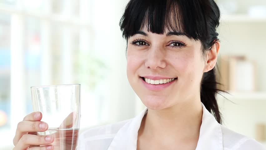 Closeup portrait of healthy young woman smiling drinking water at home