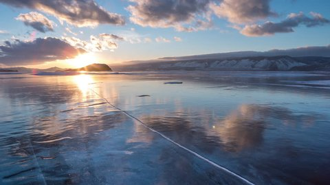 Drop a Piece of Ice on the Frozen Surface of Lake Baikal. 4K. Breaking the Ice on a Large Lake, winter break up on Lake Baikal. Blizzard on the ice. Siberian sunset.