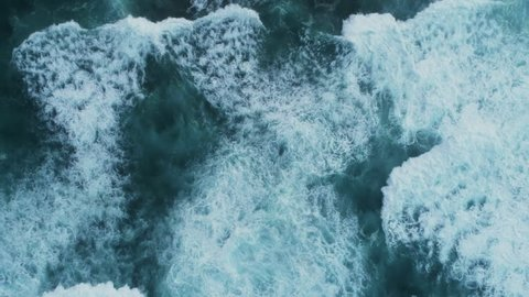 Aerial slow motion footage of waves. As the waves moves they create texture from white sea foam. The video is filmed from an overhead perspective.
