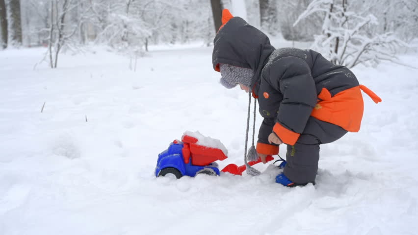acdb72fb9a9f hd00 23A child plays a toy truck in the snow. Shovel