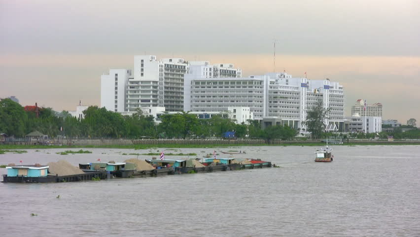 Passing a tug towing a string of barges down the Chao Phraya River in the north of Bangkok, Thailand. Building in background is the Ministry of Commerce. Canon HV20, HD 1080-50i.