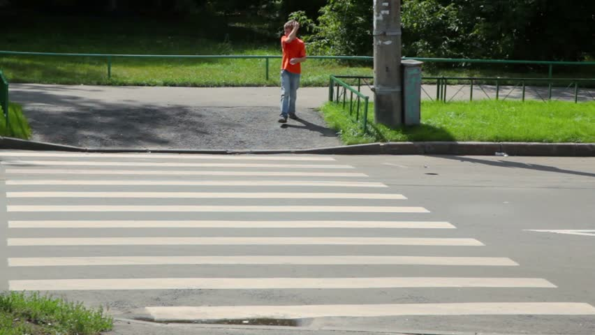 Little boy looks around and walks over road by pedestrian crossing at sunny summer day