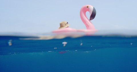 Woman lying on inflatable flamingo floating in middle of ocean girl relaxing in summer sunshine enjoying tropical vacation