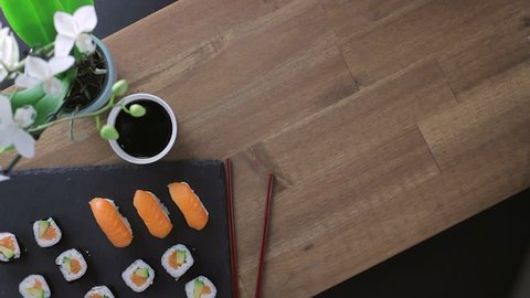 Close up of chopsticks holds sushi maki gunkan roll and place it on a plate or platter set. Served in Japanese bar restaurant. Top view, flat lay. Food background. copy space. 4K