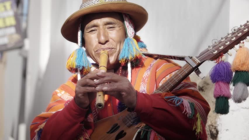 Native quechua man using a colorful handcrafted chullo and a highlander hat, playing flute, typical instrument of Peru on the alleys of Cusco | Shutterstock HD Video #24242369