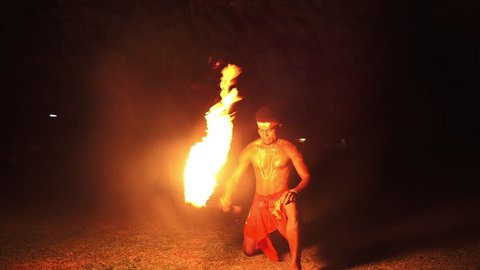 Indigenous Fijian man during during a fire dance at nigh in Fiji. Real people copy space