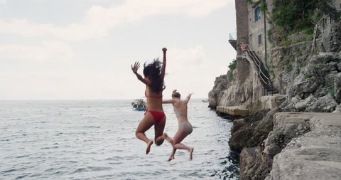 Happy Friends jumping into ocean together having excitement freedom fun action healthy travel vacation adventure Amalfi Coast Italy