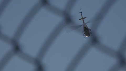 An urban police helicopter circles overhead as view from behind a chain link fence