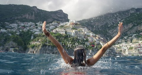 Young tourist woman jumping out of water with arms up looking at Positano town in background Swimmer girl Celebrating Italian Vacation enjoying European summer holiday travel adventure in Amalfi Italy