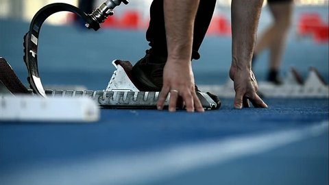 Man with leg prosthetics at the sprint start line in track and field competition