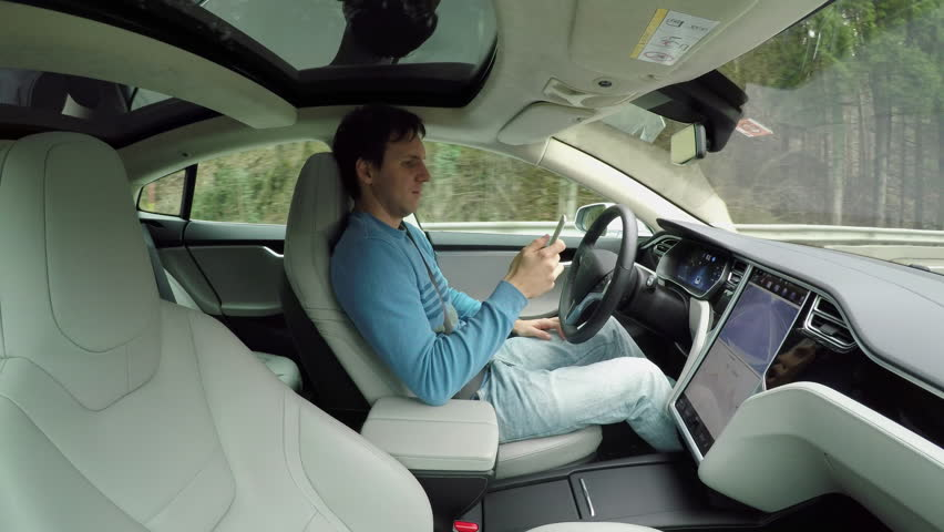 Male driver writing messages on smartphone sitting behind self-driving steering wheel in autonomous autopilot driverless electric car traveling along the countryside road. Man texting in the vehicle #24320459