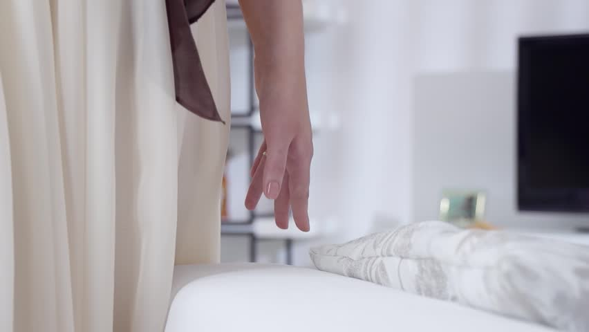 Young beautiful girl touches hand couch. A gentle touch of a hand on a white pillow in slow motion. Slow motion family home part 7 of 15.