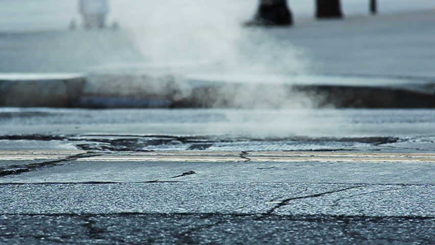 Slow motion shot of steam coming from a manhole in a street.