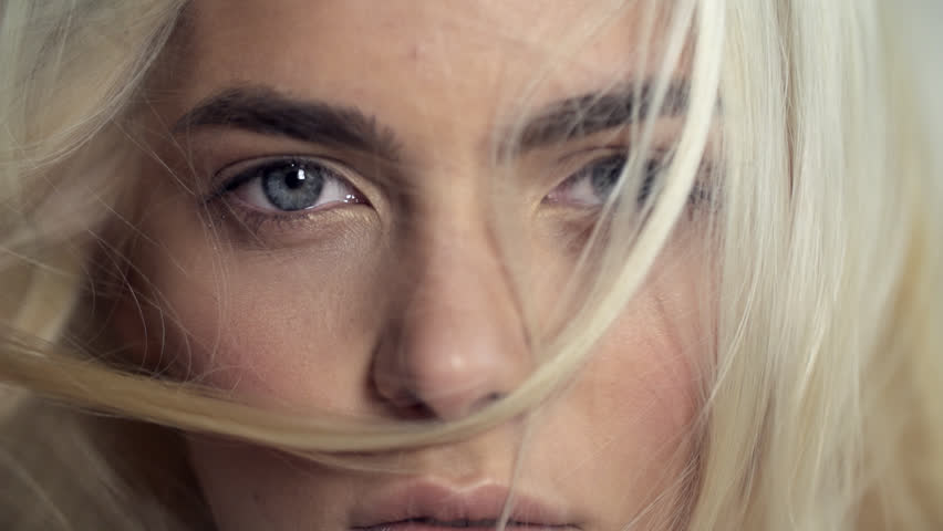 Close-up face of a beautiful blonde with blue eyes in Slow Motion #24367769