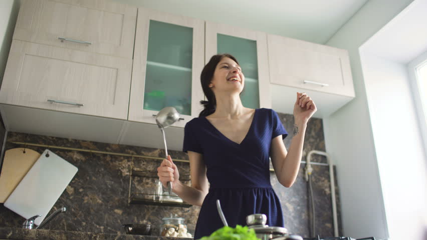 Funny Woman Housewife Cook Dance And Sing With Big Ladle While Cooking In Modern Kitchen At