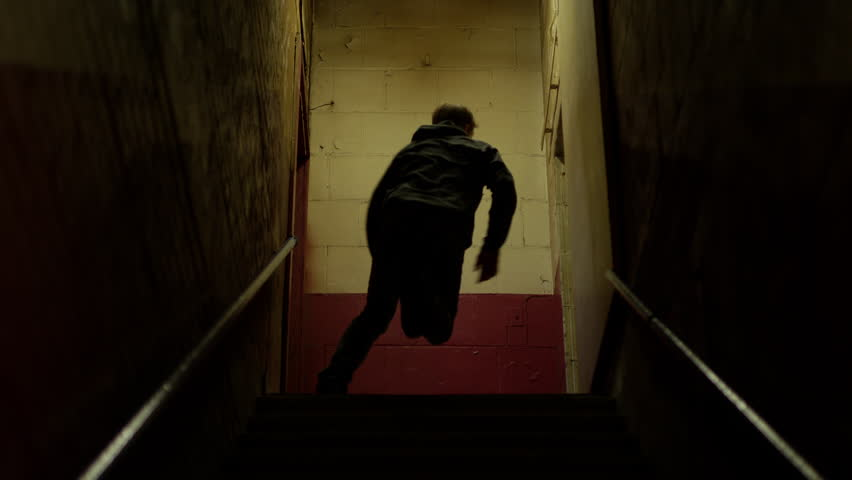Criminal hoodlum running up stairs in old building