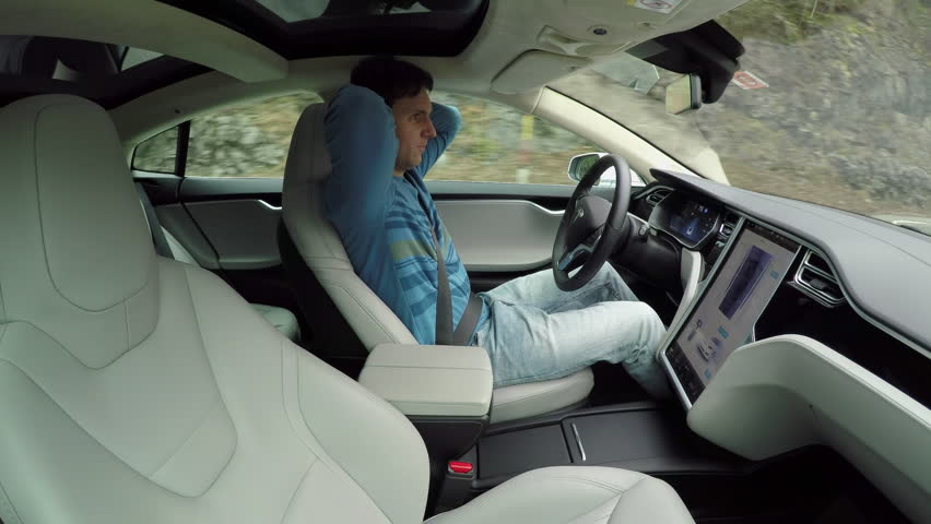 AUTONOMOUS TESLA CAR, FEBRUARY 2016: Male driver sitting behind the steering wheel and enjoying relaxing and comfortable ride in autonomous self-driving autopilot Tesla Model S driverless car #24380069