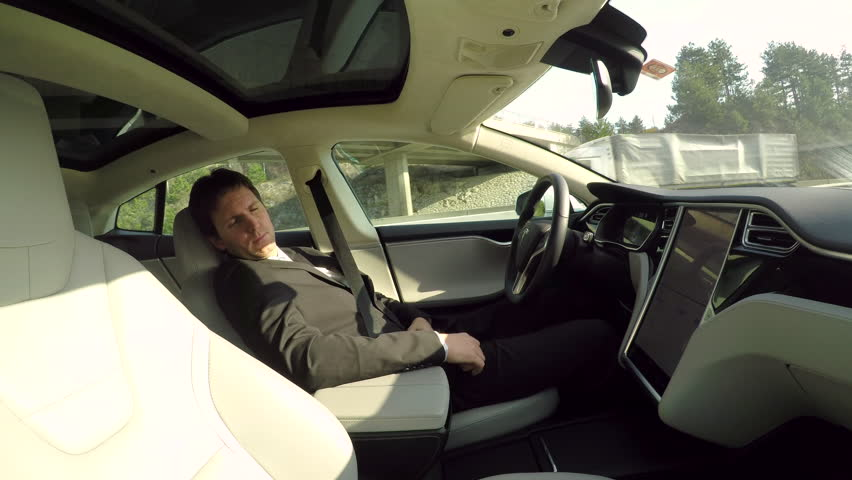 GRAZ, AUSTRIA - FEBRUARY 2nd 2017: Businessman sleeping behind self-driving steering wheel in autonomous autopilot driverless electric Tesla car. Deeply asleep man driving along the countryside road