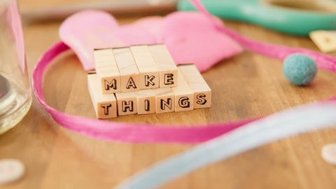 "Moving right to left along a table strewn with delightful coloured craft supplies and coming to rest on the words ""Make Things"" spelled out with wooden blocks."