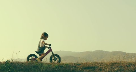 Little girl learns to keep balance while riding a bicycle, New family and baby healthy concept