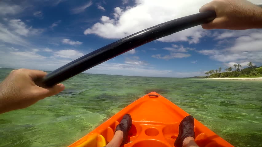 Man in a kayak, kayaking along coastline  of a tropical resort in the Coral Coast in Viti Levu Island, Fiji. POV
