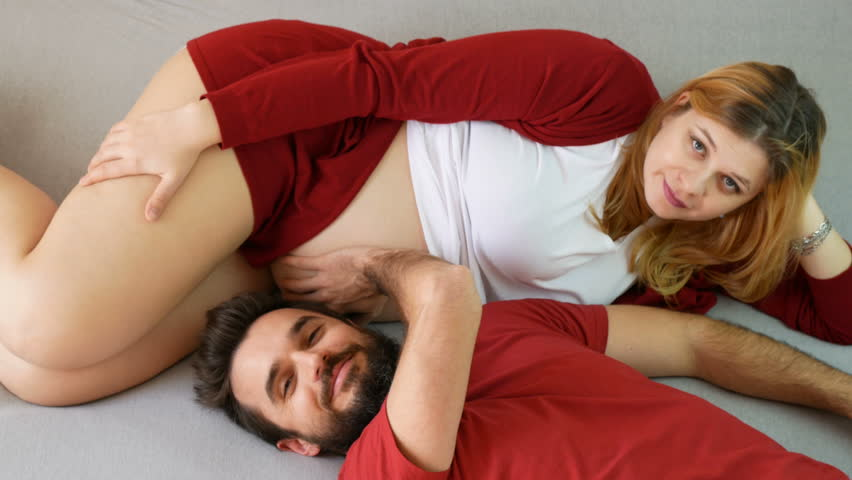 Happy pregnant couple making funny faces while relaxing together on the bed at home.   Shutterstock HD Video #24413639