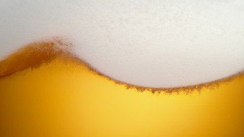 Extream close-up beer in glass. Foam moving. Shot with high speed camera, phantom flex 4K. Slow Motion.