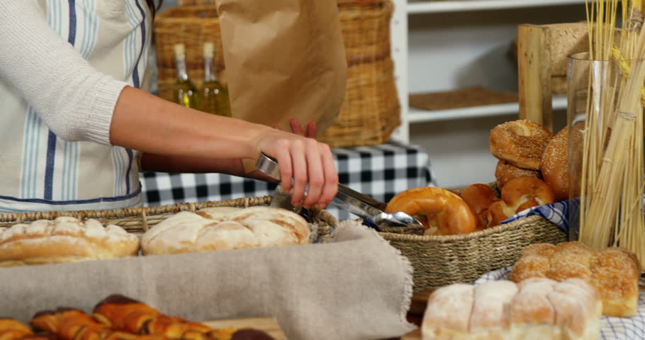 Smiling female staff packing doughnut in paper bag at bakery section of supermarket
