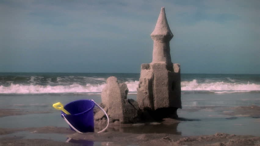 Great beach and ocean shot with sand castle that crumbles with the tide. Nice color toning. South Carolina.
