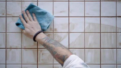 Tattooed male hand wipes out with blue micro fiber cloth dried and dirty tile adhesive from custom made kitchen table with white glance ceramic, top view