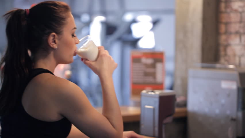 Barman in fitness center give protein shake to young slim beautiful woman. In sports center redheaded lady with ponytail in black sportswear sitting at wooden bar, drink nutrition milk cocktail as