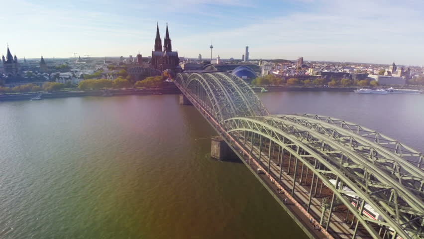 Cologne famous bridge aerial, German city Koln sight seeings Cathedral, during sunset. Opera and railway station, dramatic flight over travel tourist attraction Cologne bridge with trains and people