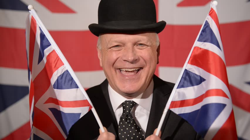Traditional British city worker / businessman with a happy expression on his face, waves two small Union Jack flags, in the background is a large Union Jack blowing in the breeze.